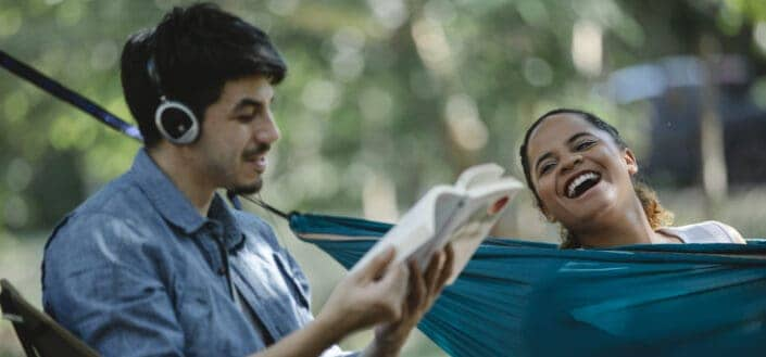 Happy multiethnic couple with book and hammock