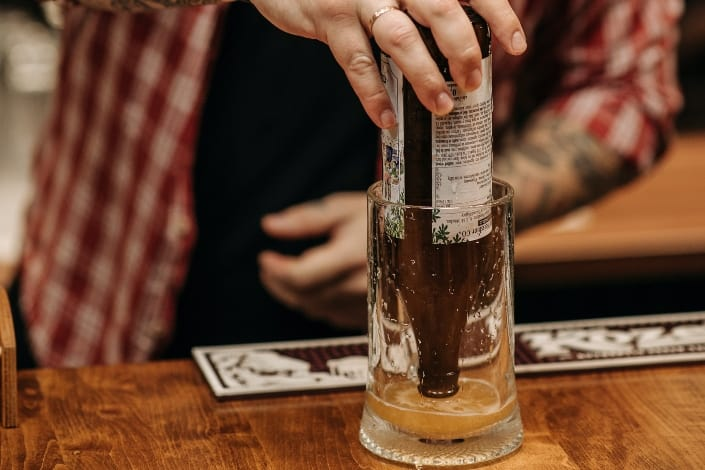 man pouring beer on hopside down glass
