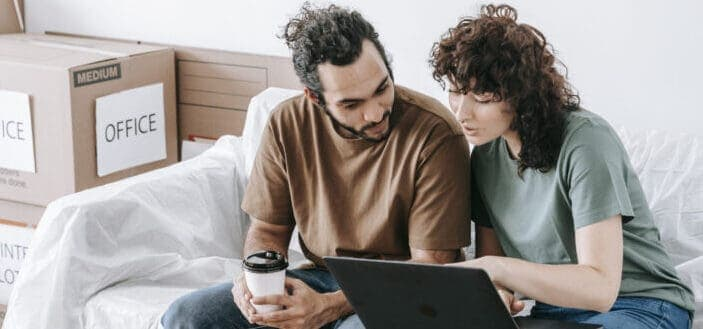 couple discussing something while using laptop