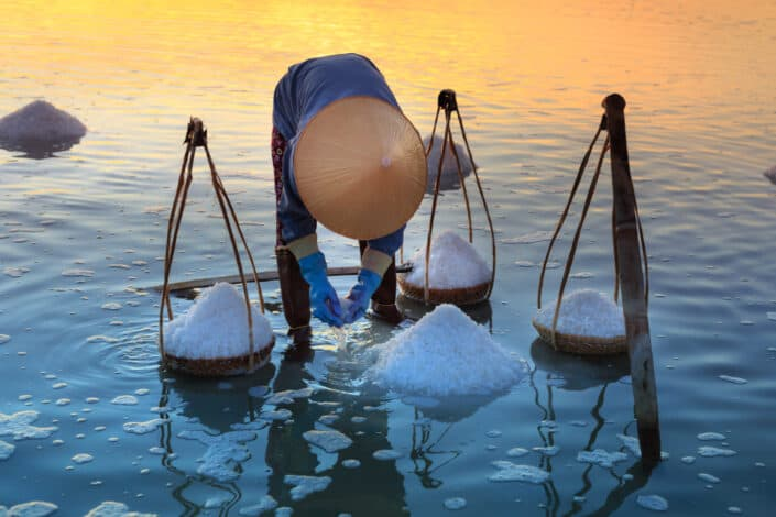 Person collecting salt on body of water