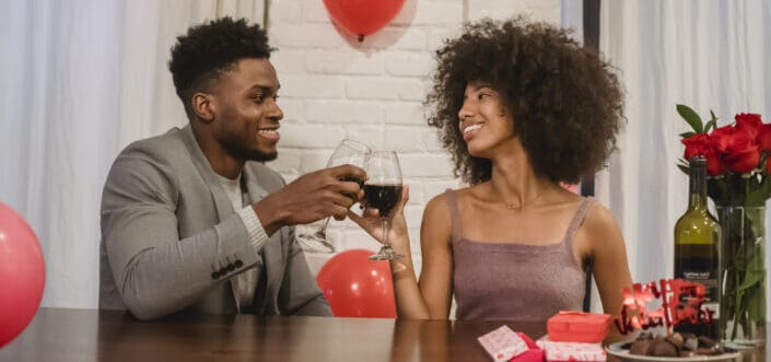 Man and woman tossing glasses of wine, celebrating Valentine's day together