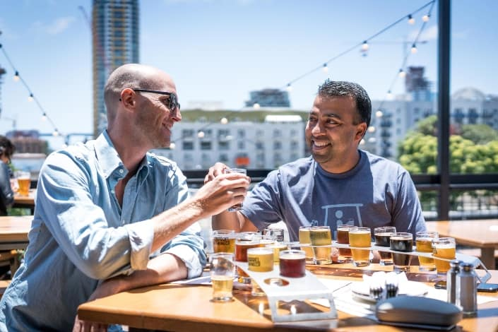 two men taste testing different beers