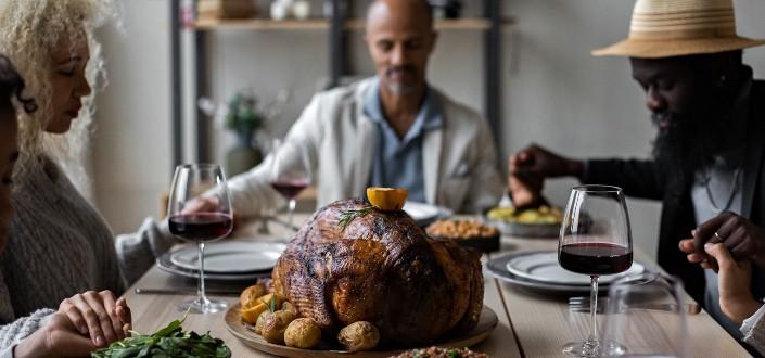 diverse people praying for their thanksgiving meal