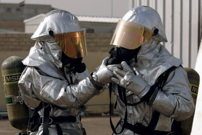 Two uniformed people breathing through oxygen supply
