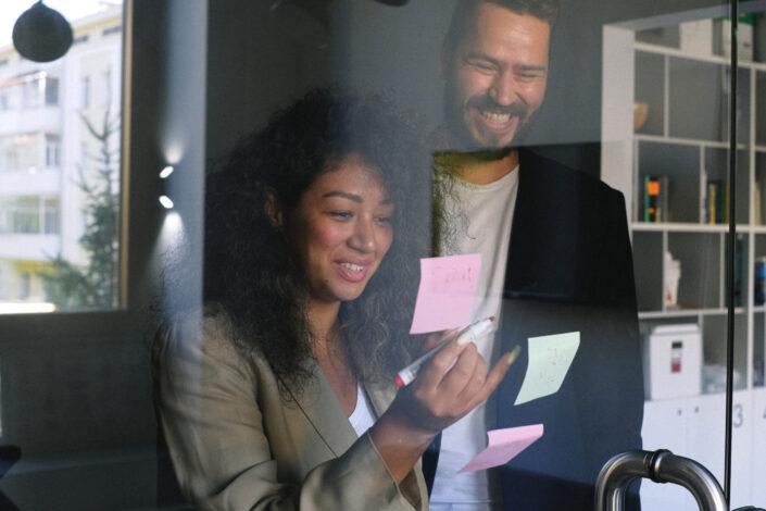 Woman amusingly sticks post-it on glass wall