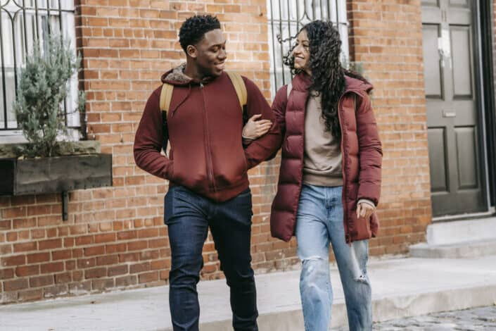 glad multiethnic couple walking on street