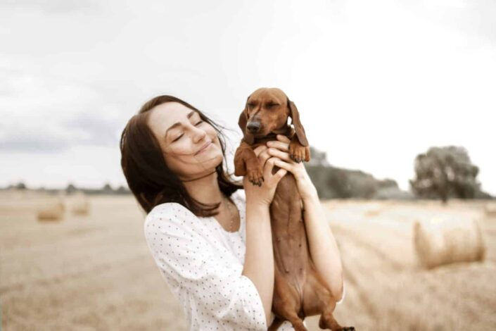 Woman carrying her dog happily