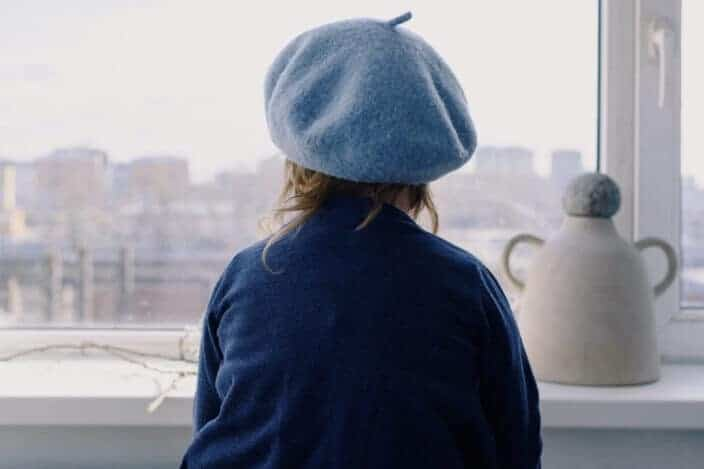 Little girl in beret looking out window
