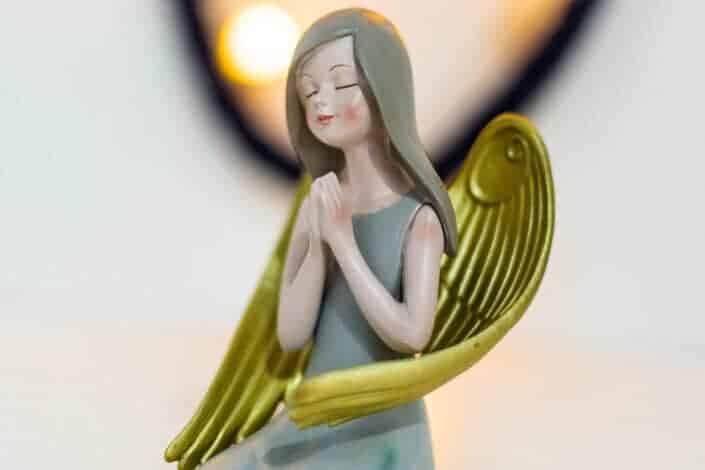 figurine woman in green dress and wings