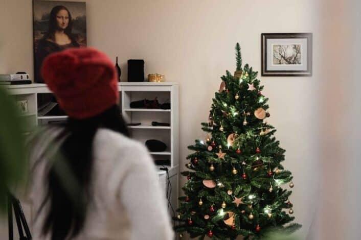 a woman standing near a christmas tree