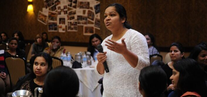 Woman in white asking question using a microphone.