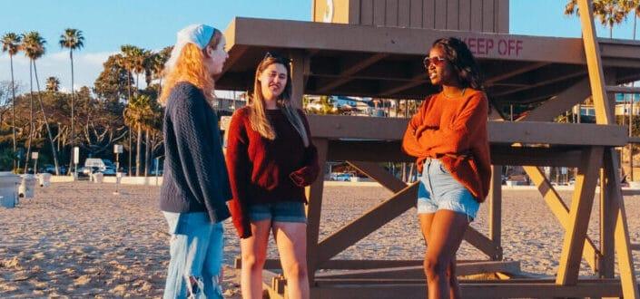 Three women standing on beach sand