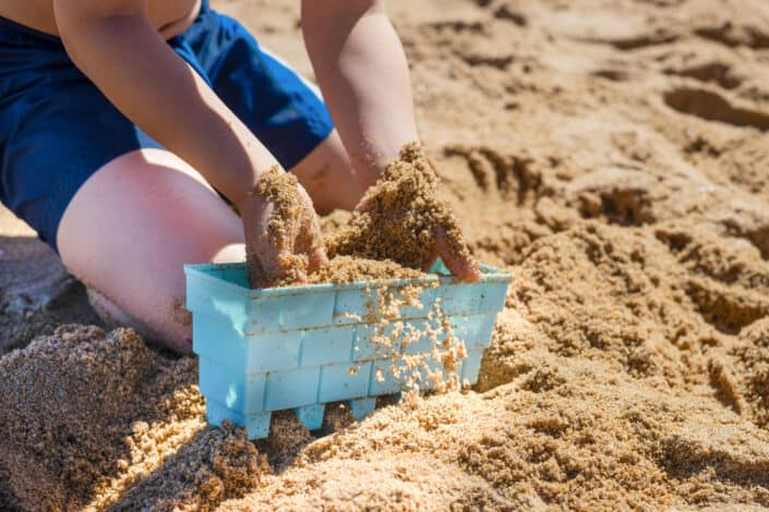 A person scooping sand by hands