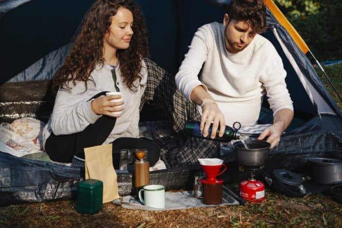 hikers preparing hot drink in campsite