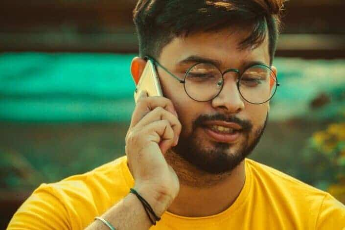 a man in a glasses and yellow shirt talking to someone on his phone