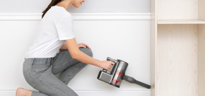 woman cleaning behind cabinet using an electronic tool