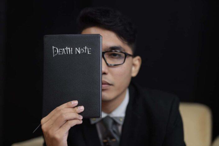 man in black suit holding black notebook