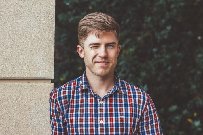 a winking man in a checkered polo shirt