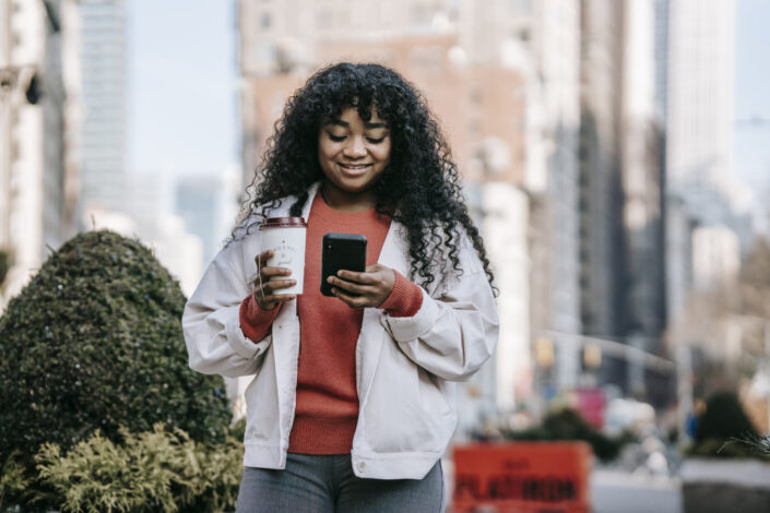 smiling woman with coffee browsing smartphone on street