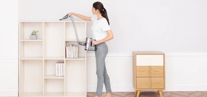 lady cleaning the top of a shelf using an electric cleaner