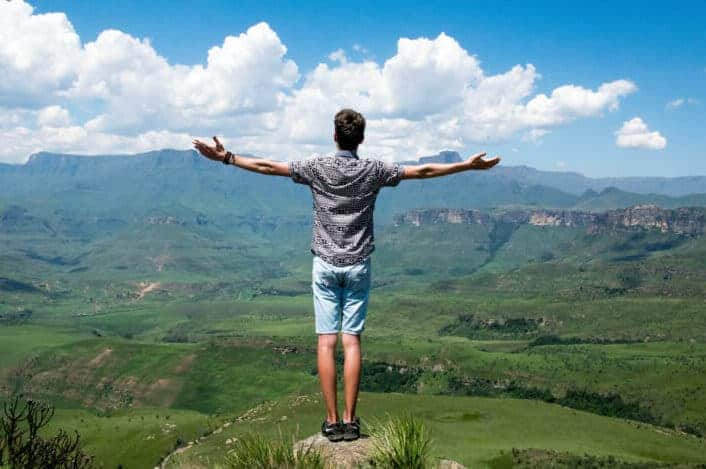 Man spreading arms on top of mountain