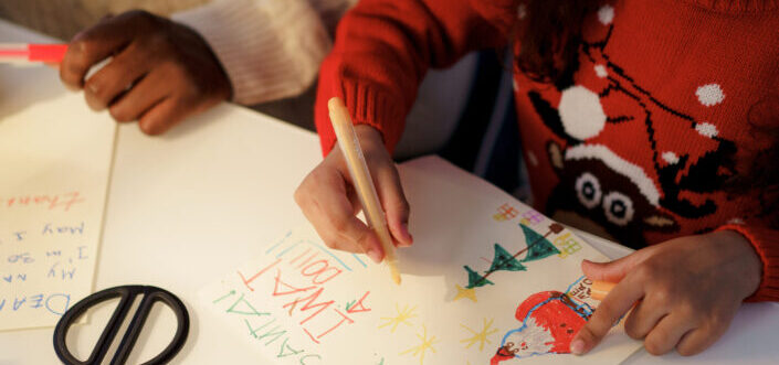 Two kids writing a Christmas letter.
