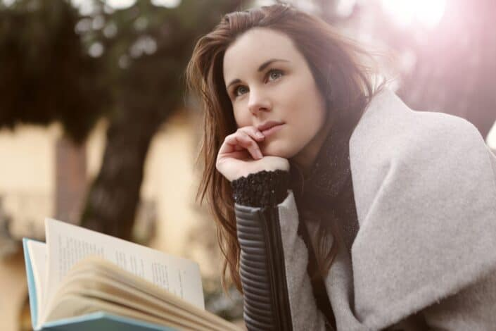 Woman paused from reading and thinking something