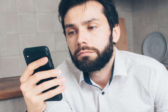 a serious looking man reading something on his phone