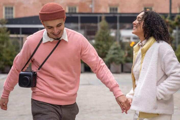 couple smiling and holding hands on urban street