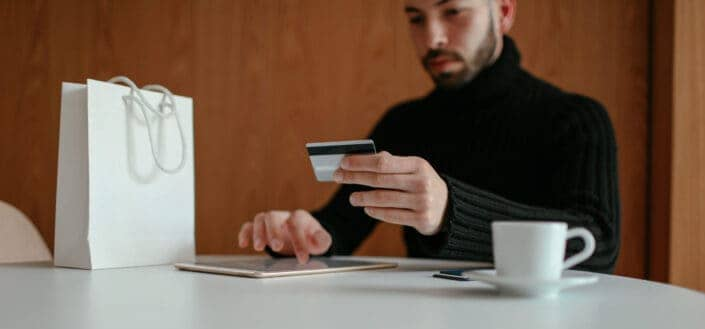 man with a card on his hand thinking of an online purchase