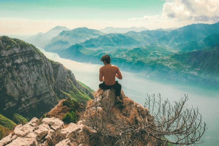 shirtless guy sitting on a mountain cliff