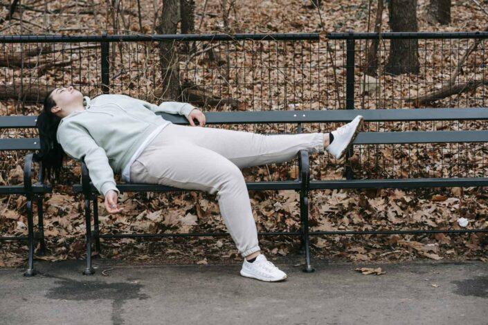 woman lazily lying on a park bench