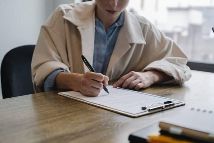 woman writing in clipboard