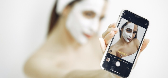 woman doing selfie with a skin care product on her face