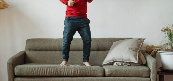 Person jumping up and down on a couch.