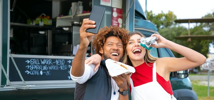 two friends having selfie with their food in front of a food truck