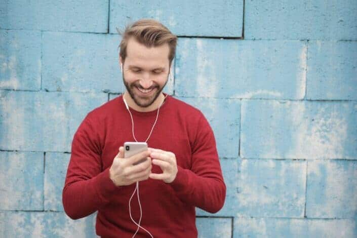 cheerful man watching videos on his phone