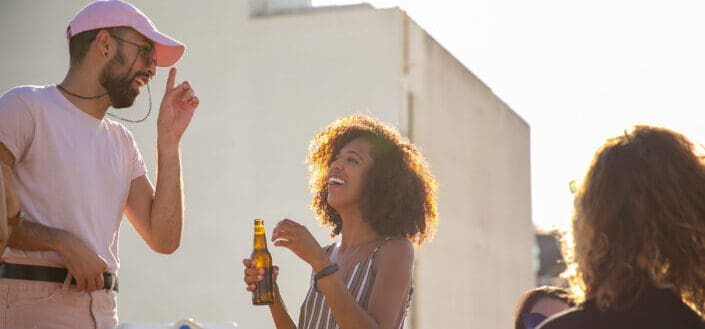 friends drinking beer and chatting on rooftop
