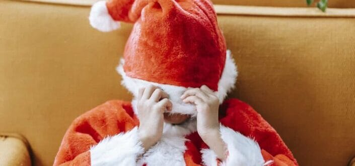 Little kid in Santa costume covering face