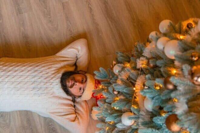 Man lying on the floor underneath a Christmas tree. - home alone trivia