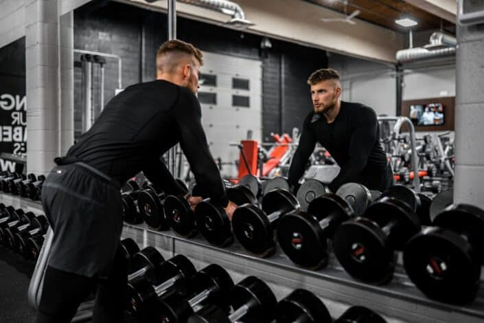 Man staring at his mirror reflection at gym.