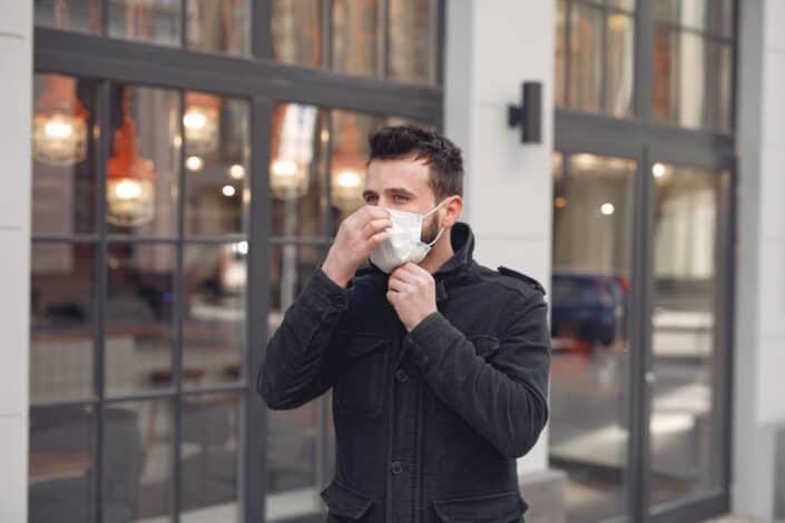 Man wearing facemask while walking on street.