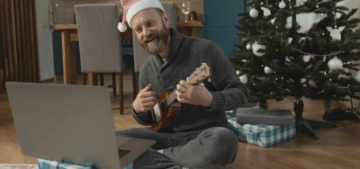 Man with a santa hat playing guitar