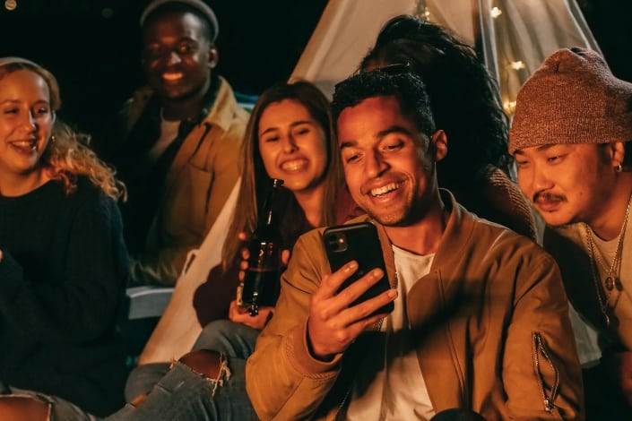 man showing his mobile phone to his friends