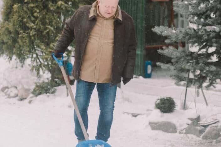 Old man shoveling snow deposits.