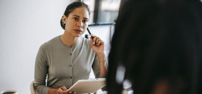 serious psychotherapist listening to client complaints