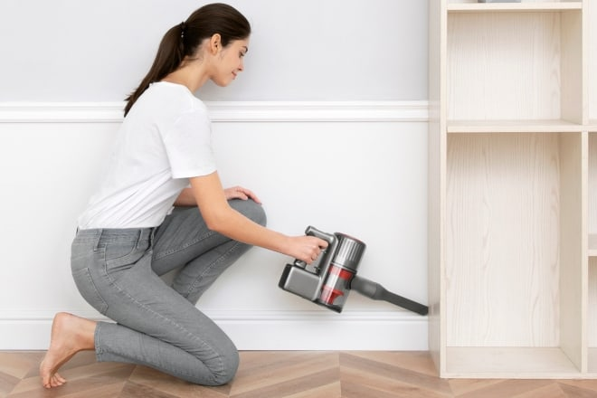 woman cleaning the side of cabinet - Roborock H7 Cordless Stick Vacuum Review