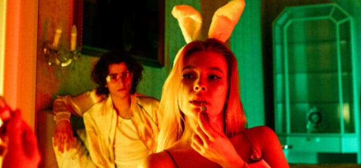 a man staring at a dressed up woman with a bunny ears headband