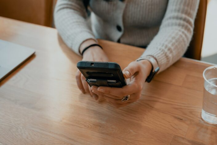 woman in sweater holding black smartphone