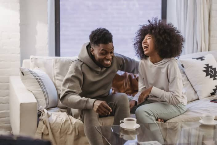 young couple having fun at couch at home